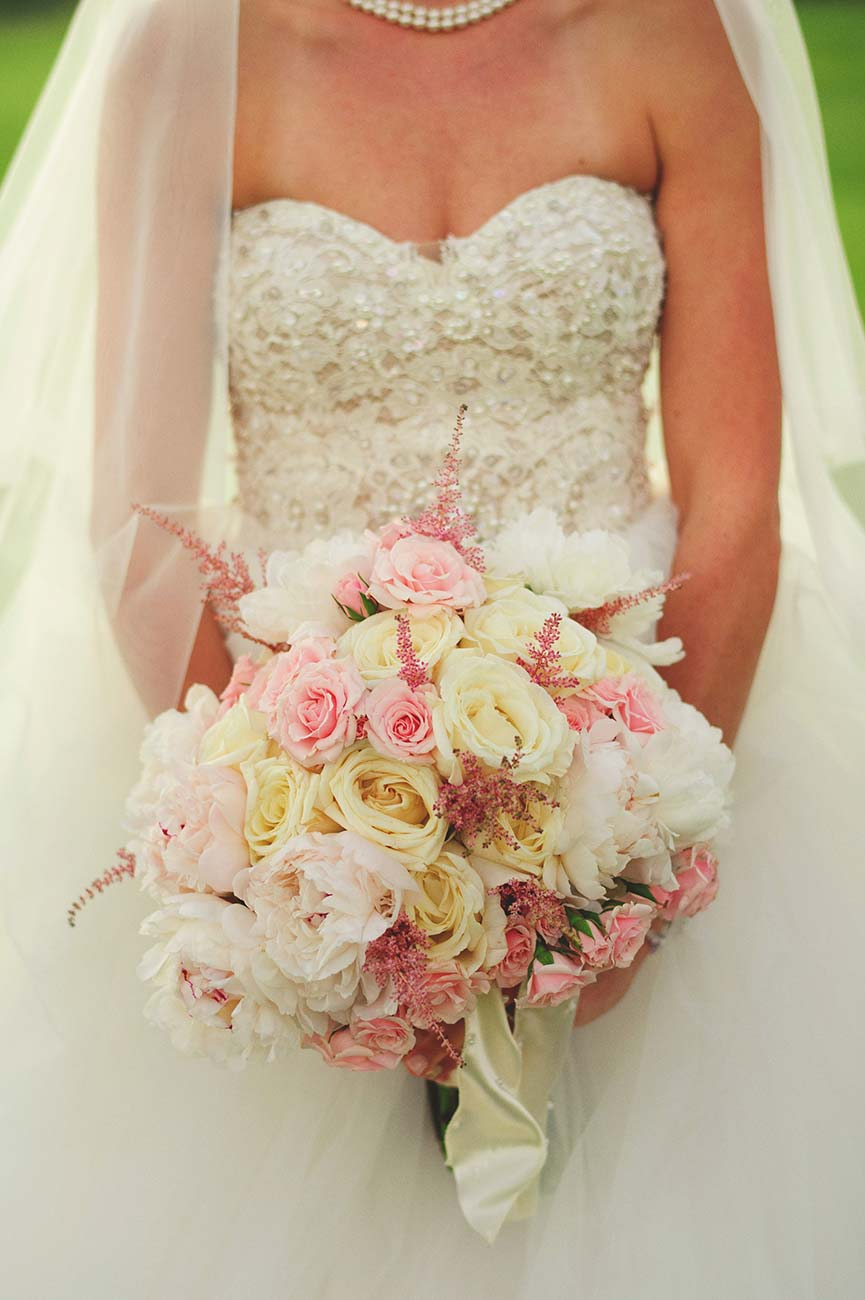 Bride holding her white and pink and light yellow bouquet against her gown