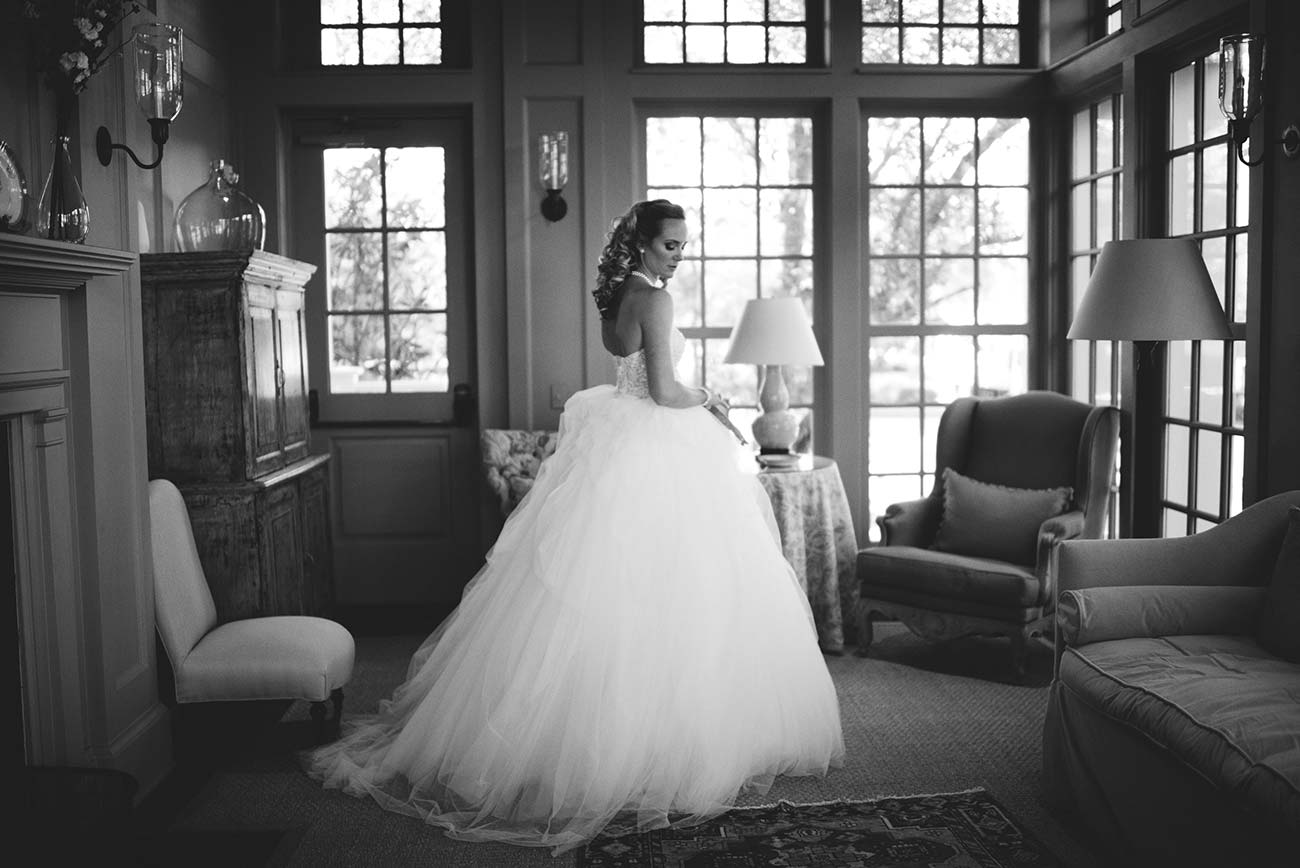 Black and white full length portrait of a bride in a living room against windows