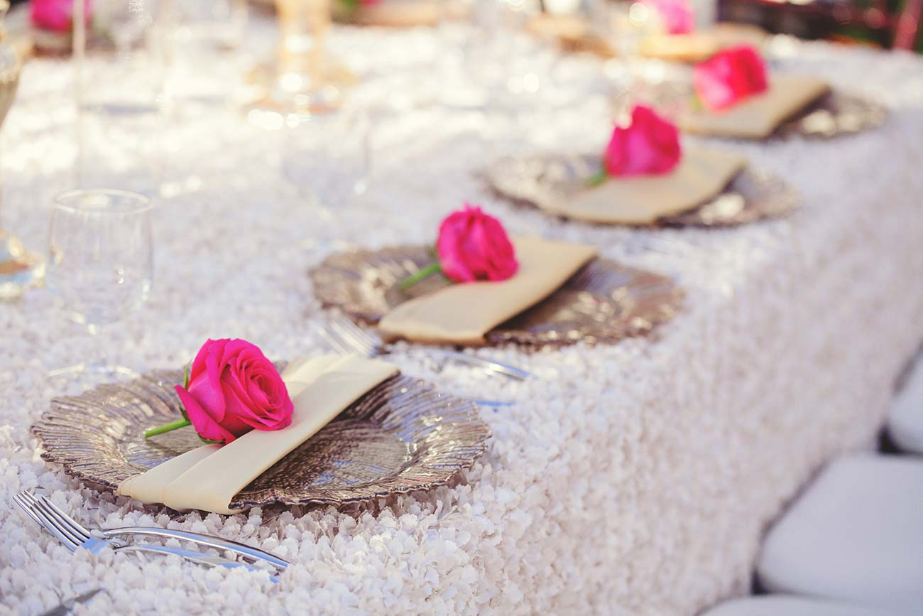 Wedding day reception table top design, plates with a single rose on each one