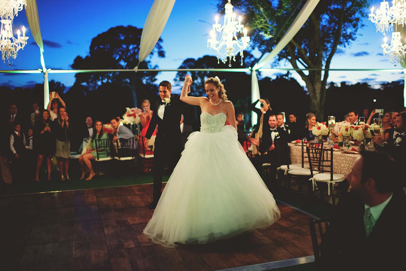 Bride and groom holding hands and entering their wedding reception tent, guests clapping around them