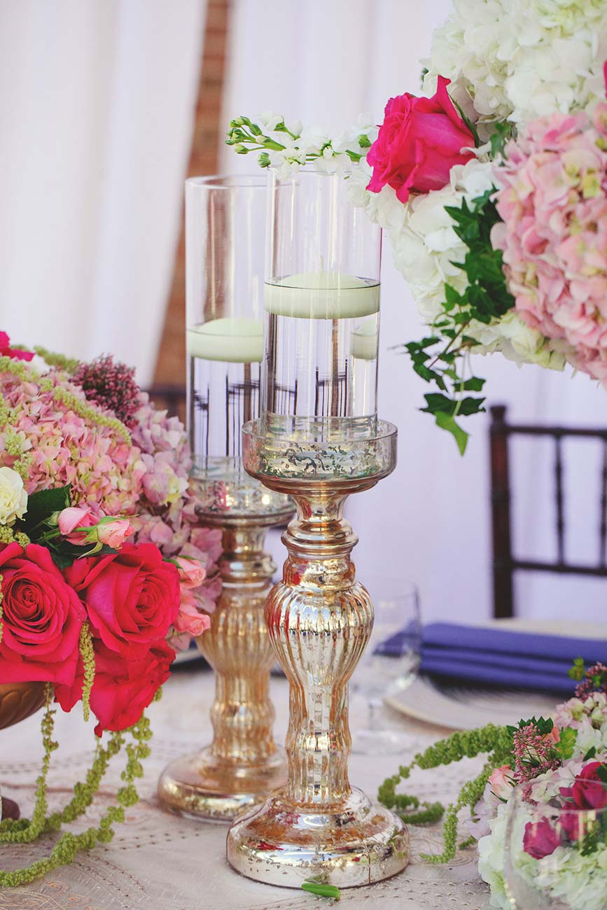 Wedding reception table top design with floral arrangements, dinnerware and candles