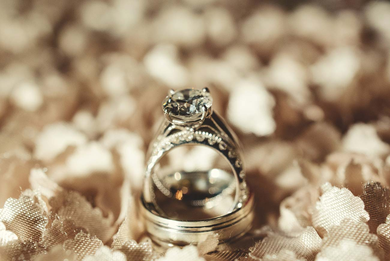 Bride and groom's wedding ring set against fabric background