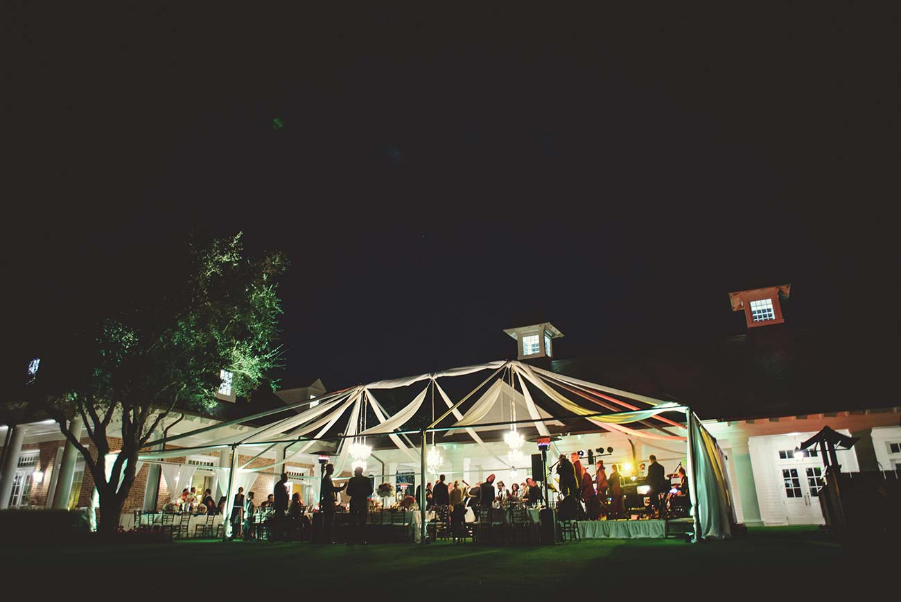 Night time view of outdoor wedding tent with guests