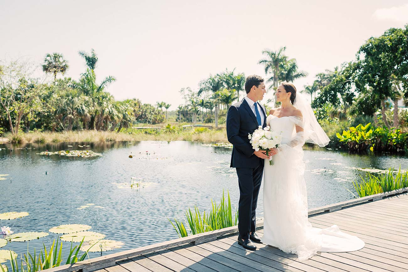 Bride and groom looking at each other, standing on a wooden boardwalk overlooking a small lake