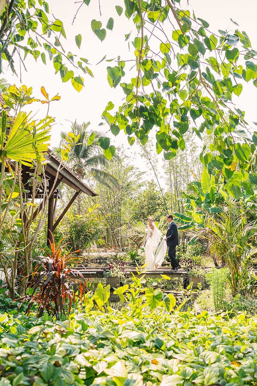 Far away portrait of bride and groom in a heavily landscaped location