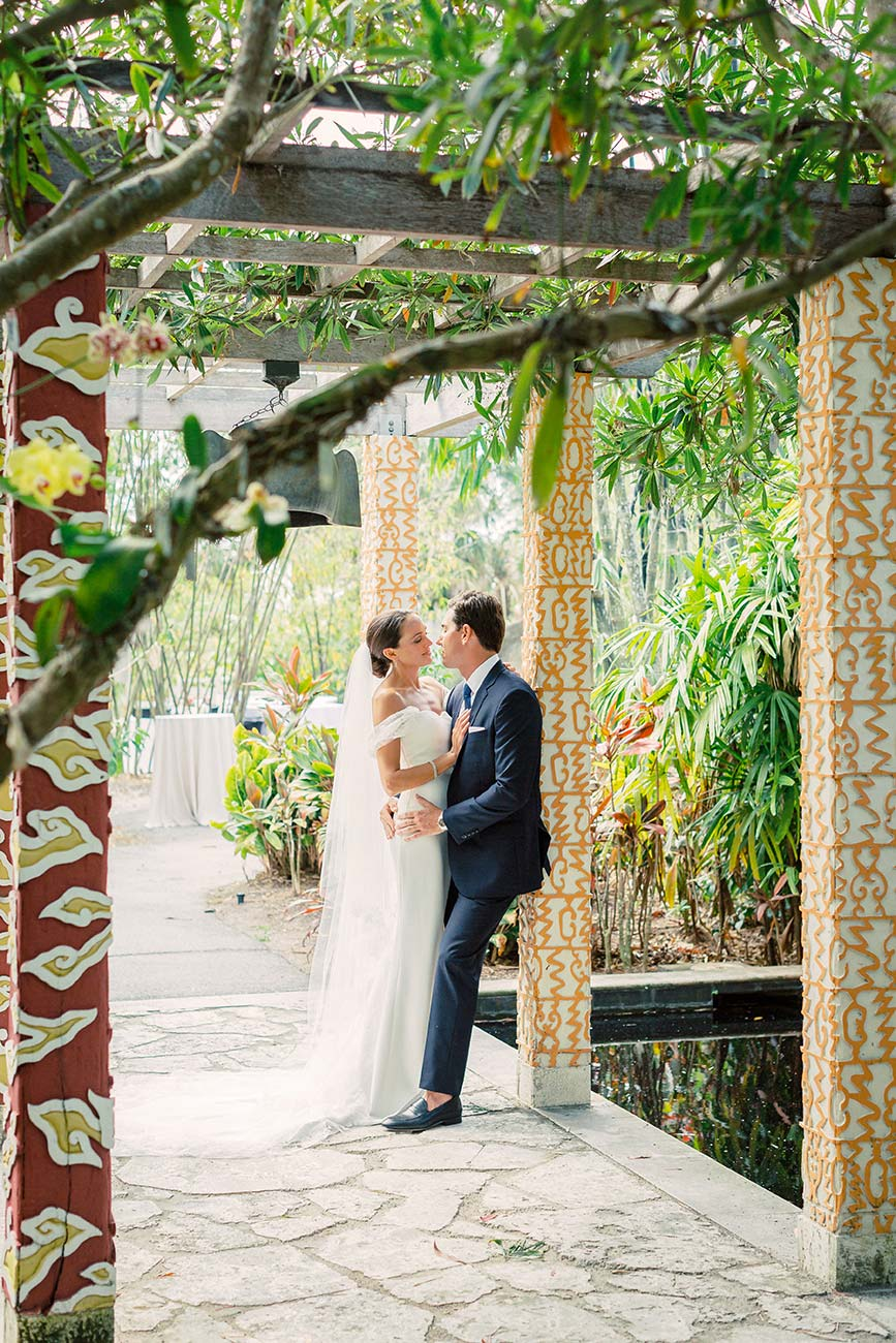 Bride and groom hugging each other in an outdoor patio