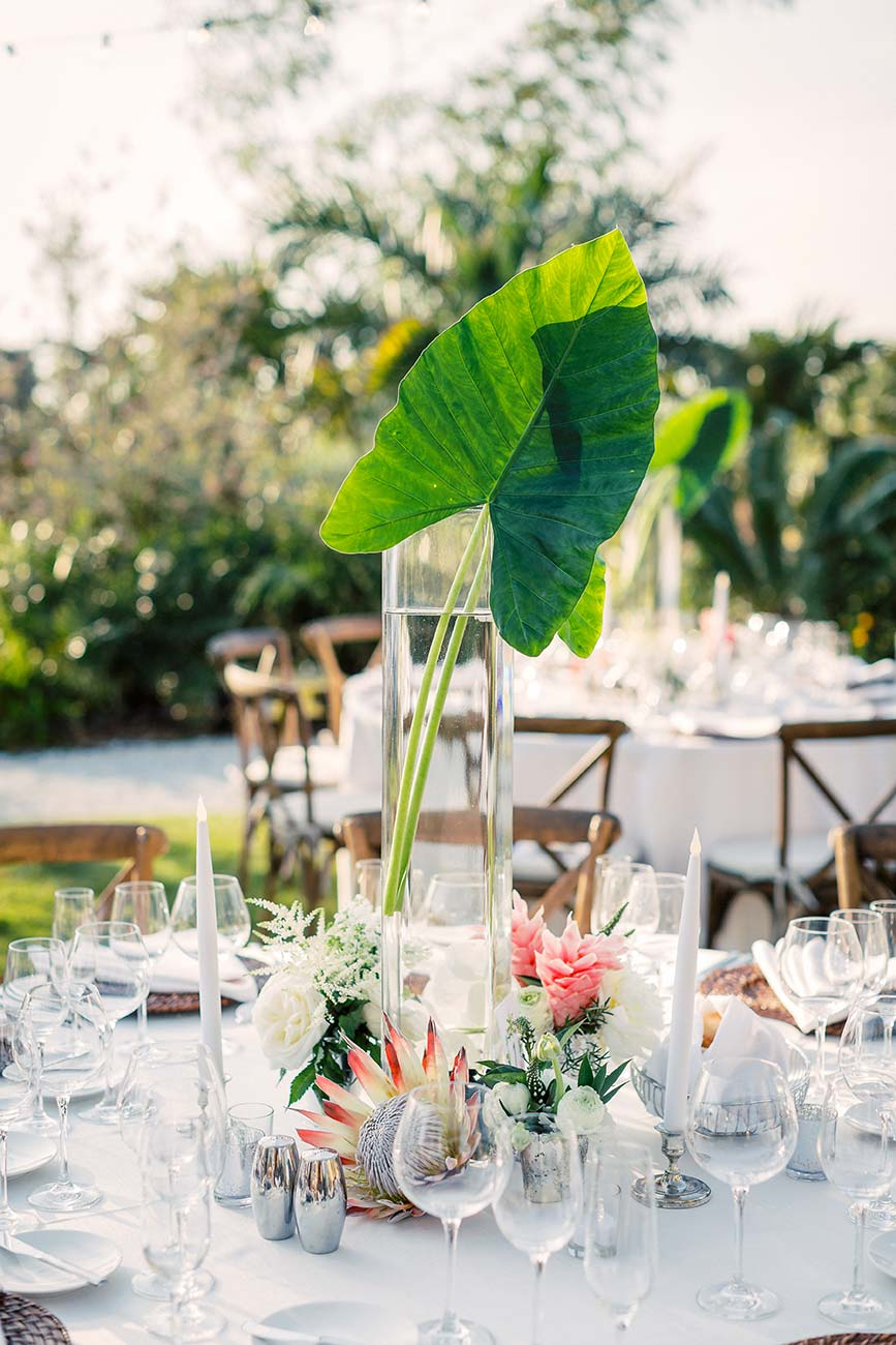 Outdoor wedding reception tablescape with flowers, dinnerware and crystal