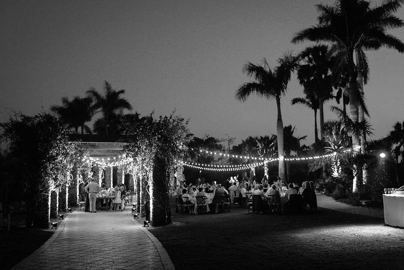 Black and white image of outdoor wedding toasts