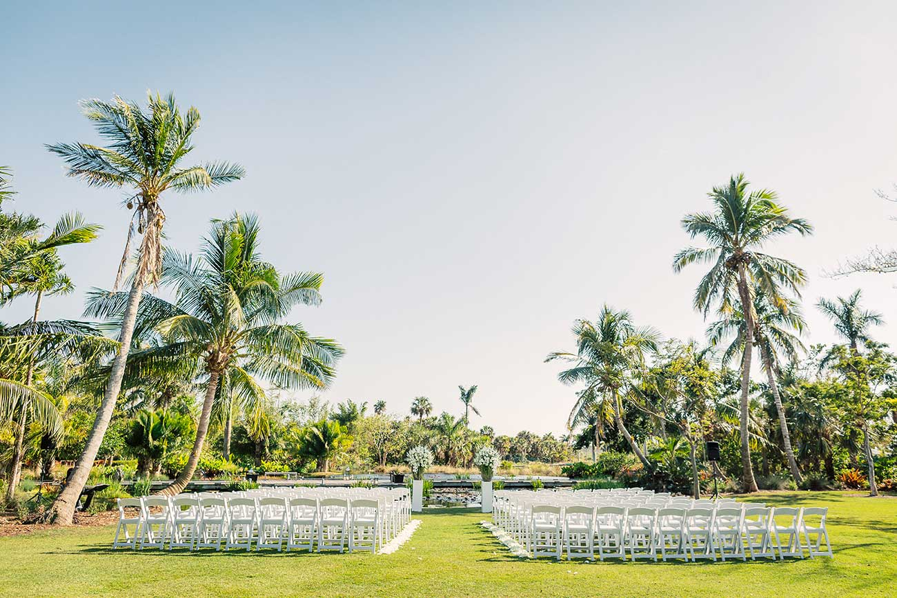 Outdoor wedding ceremony setup on lawn with palm trees