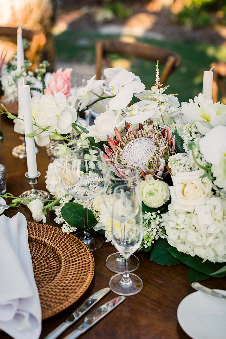 Wedding reception tablescape with flowers, dinnerware and crystal