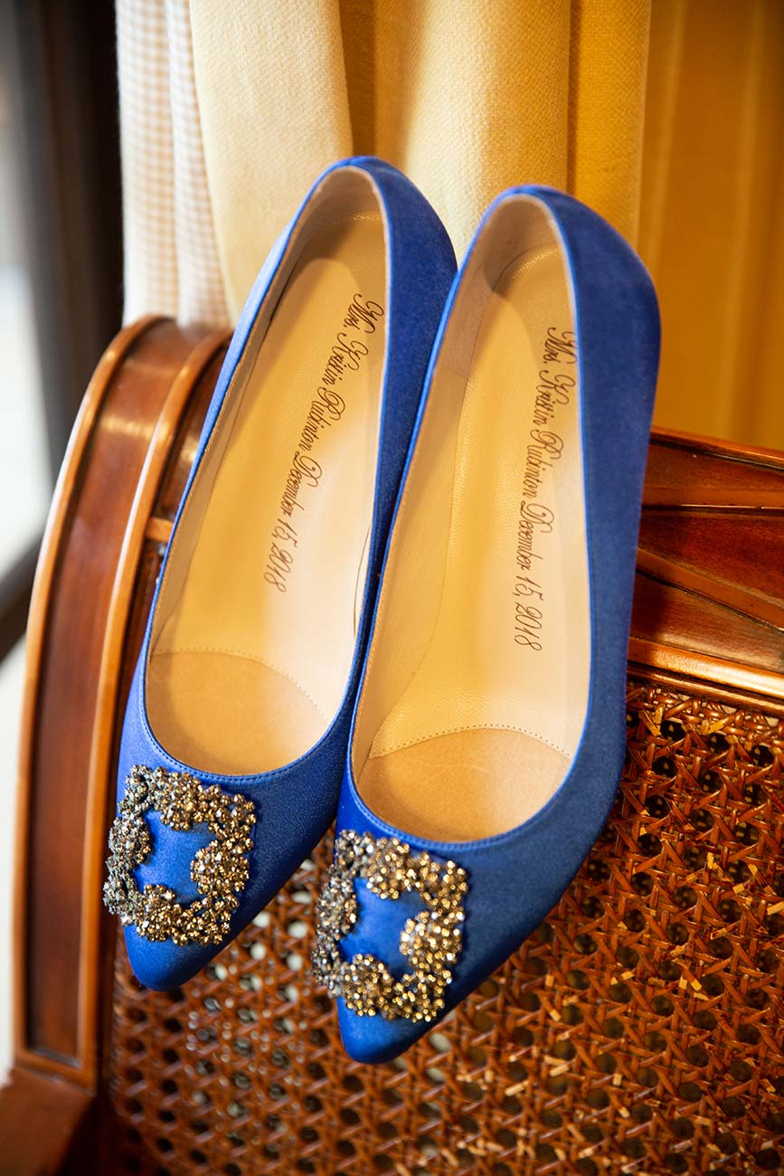 Image of bride's blue wedding day high heeled shoes hanging off the back of a brown chair