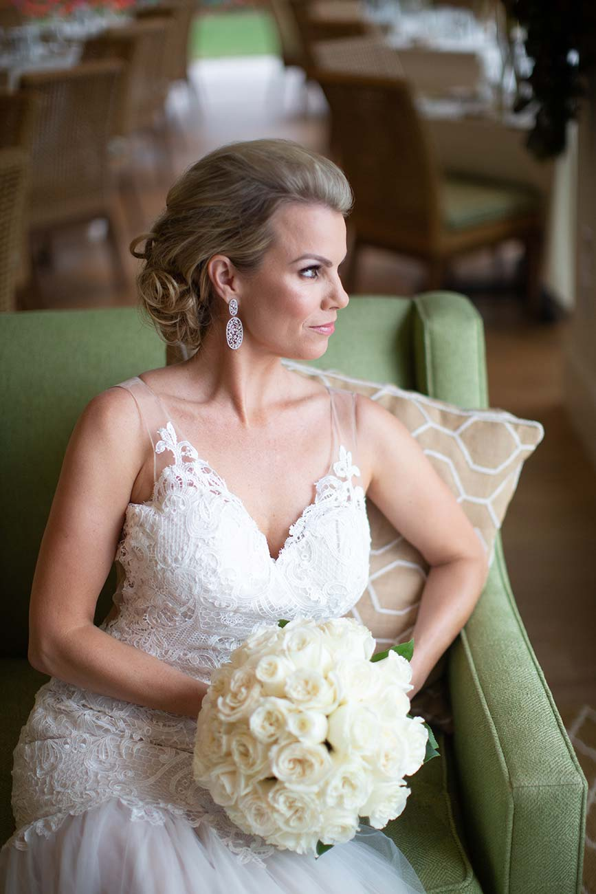 Bride with her wedding bouquet, sitting on a chair looking out the window