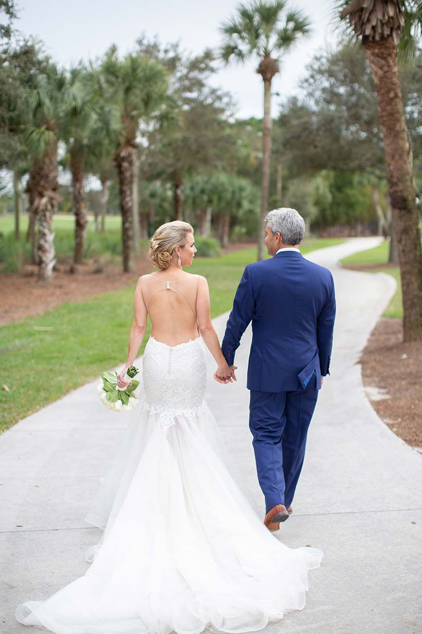 Bride and groom walking away from camera, holding hands