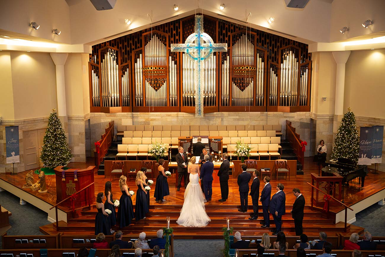 Bride and groom, wedding party and priest during wedding ceremony at church