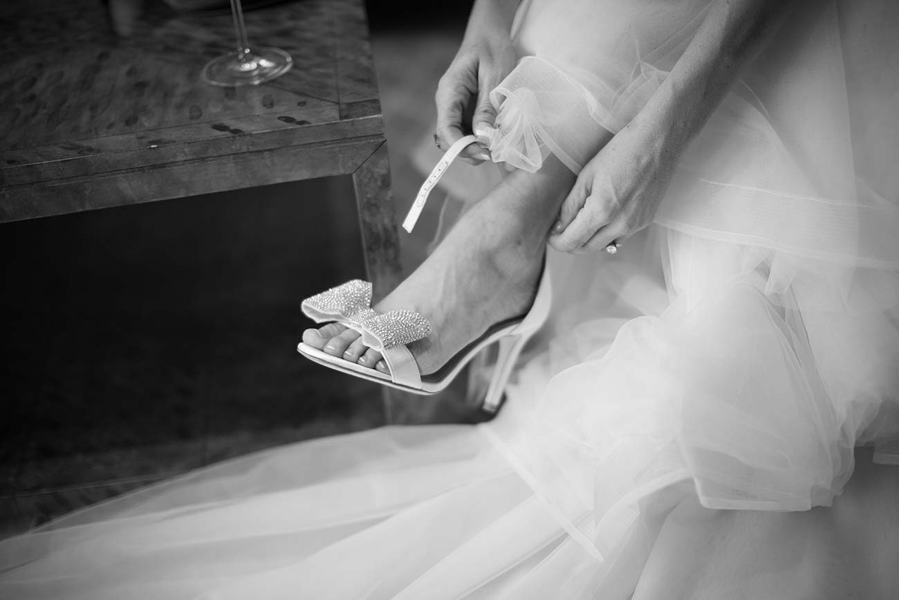 Close up of bride putting on her wedding day heeled shoe