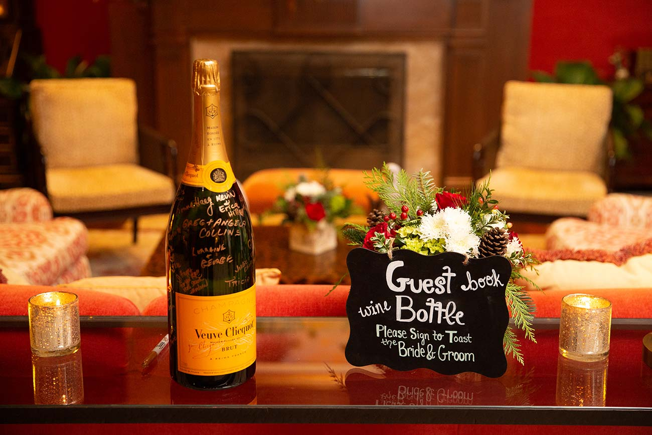Bottle of Veuve Clicque champagne signing bottle and Guest Book instructions sign on console table