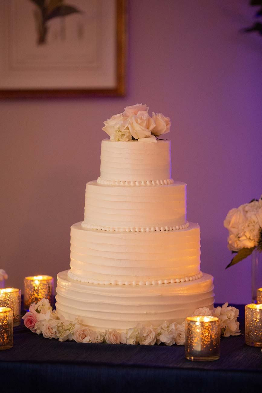 4-tiered white wedding cake with three roses on the top tier, surrounded by tea candles