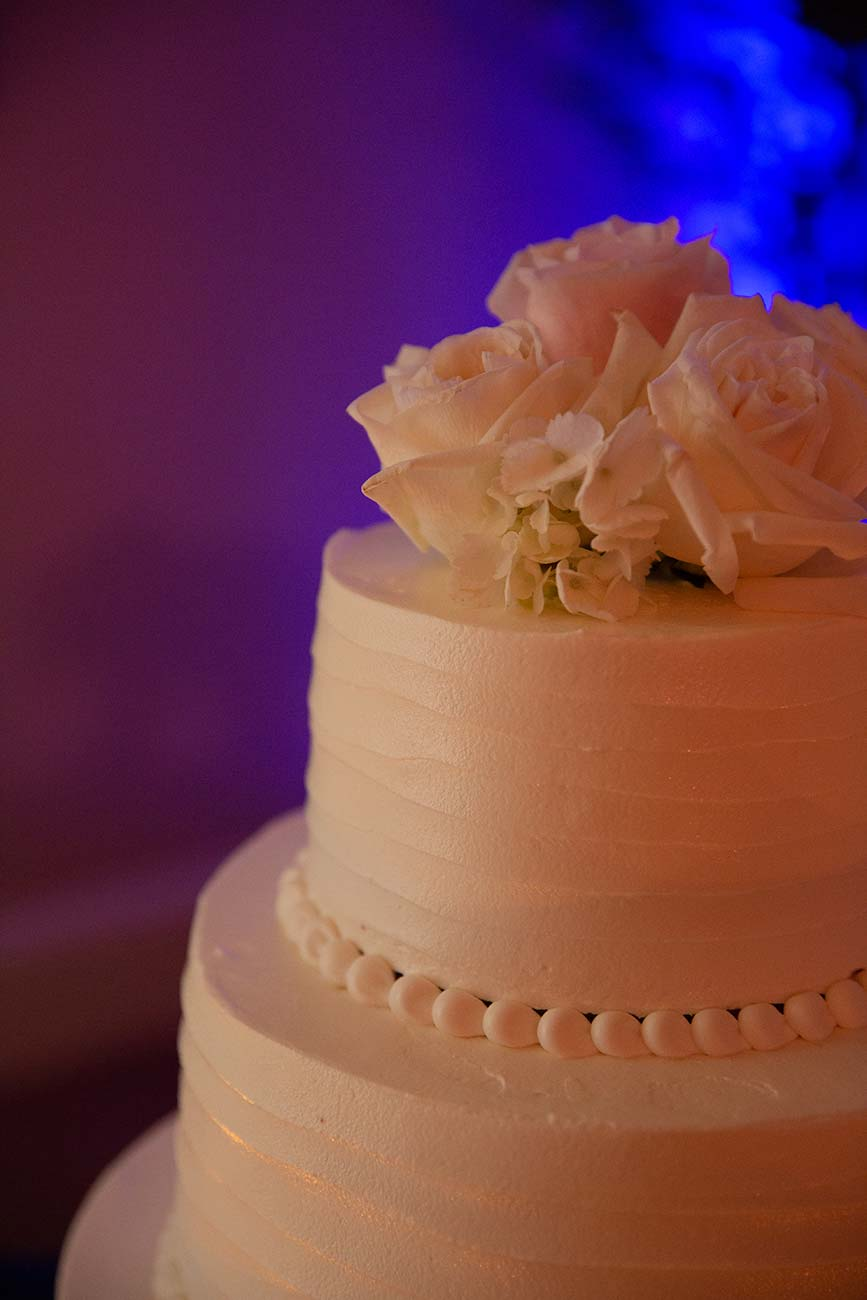 Close up of wedding cake with three roses on the top tier