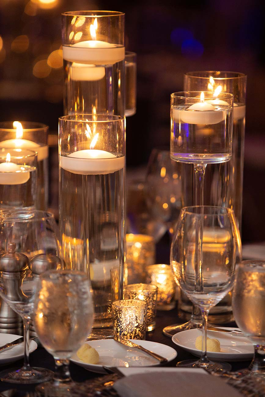 Tabletop view of wedding guest table covered in crystal candle holders and table number