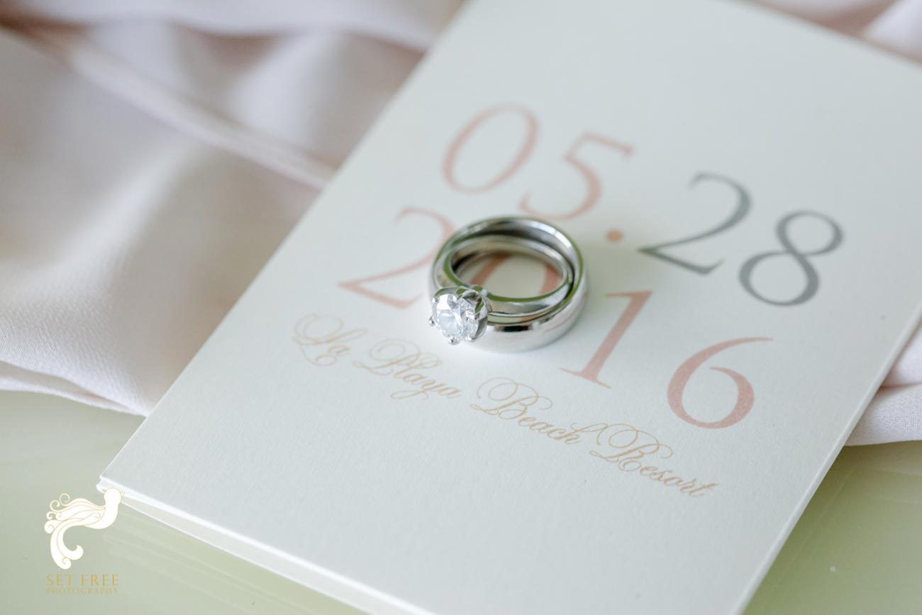 Wedding ring and band over wedding invitation