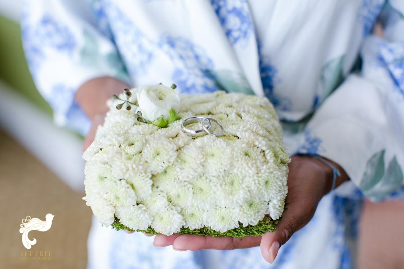 Close up of white flowers with wedding bands on top