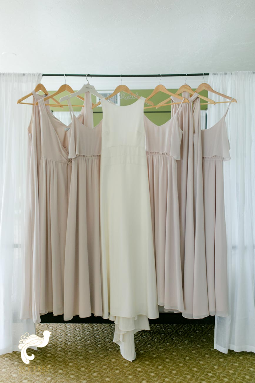 Bridal gown and bridesmaids dresses hanging off bed posts