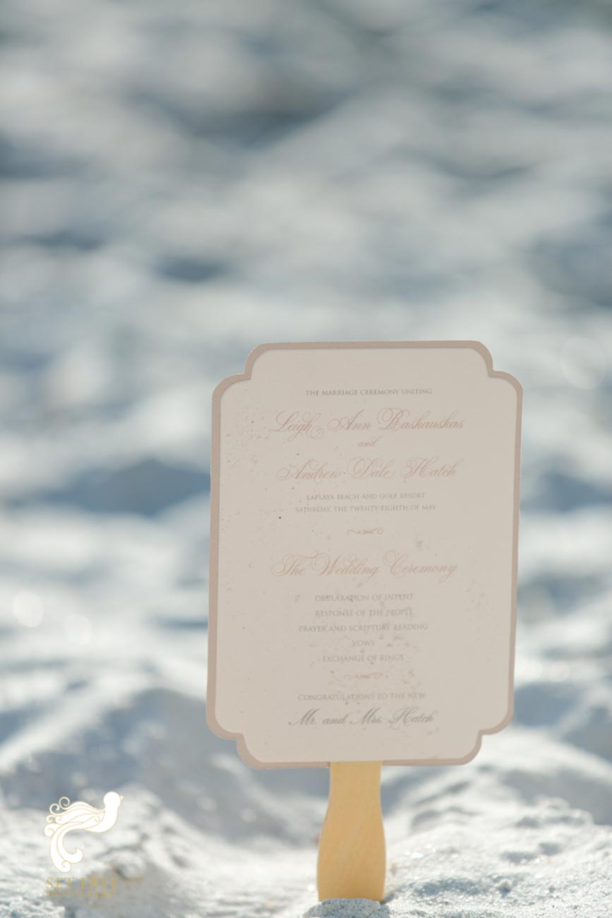 Wedding invitation placed in sand on beach