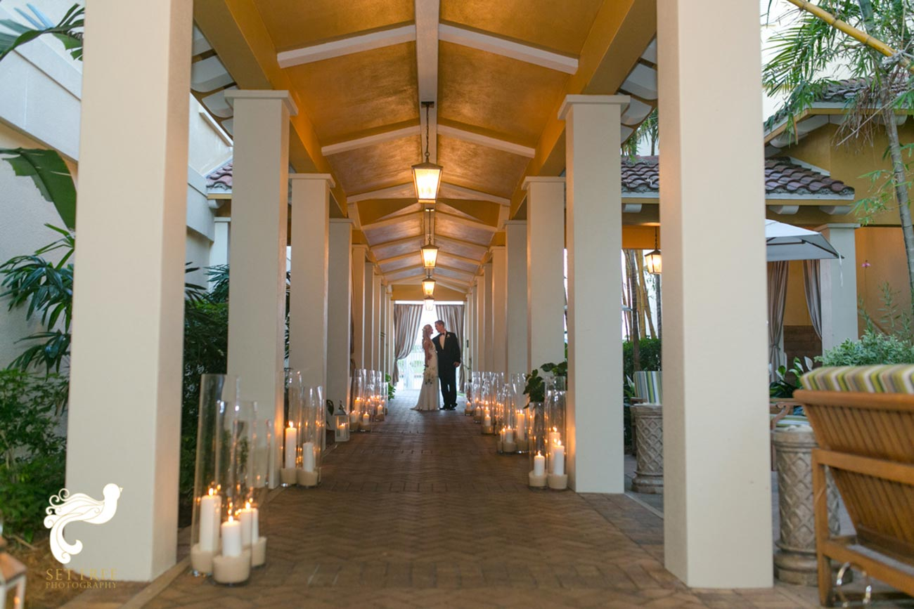 Bride and groom together at the end of a candle-lit outdoor hallway