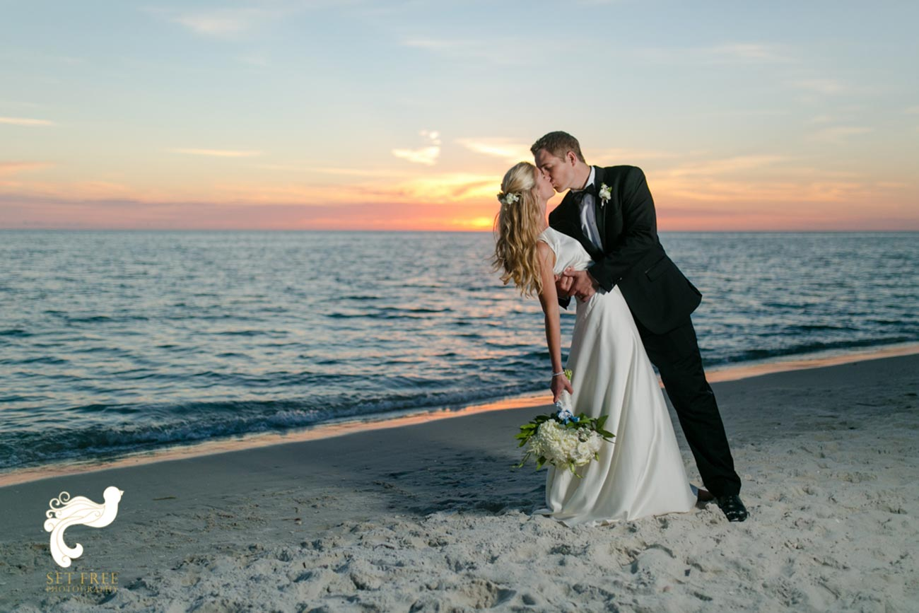 Bride and groom kissing on the beach with sunset behind them