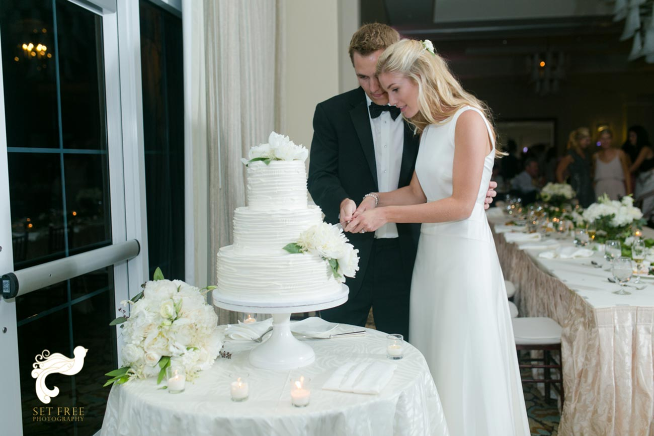 Bride and groom cutting a 3-tiered wedding cake with guests behind them