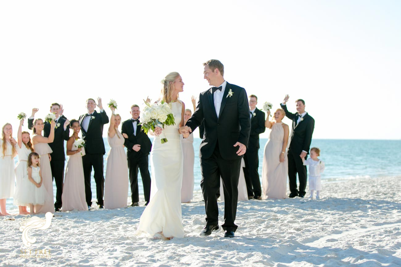 Bride and groom walking with wedding party behind them on beach