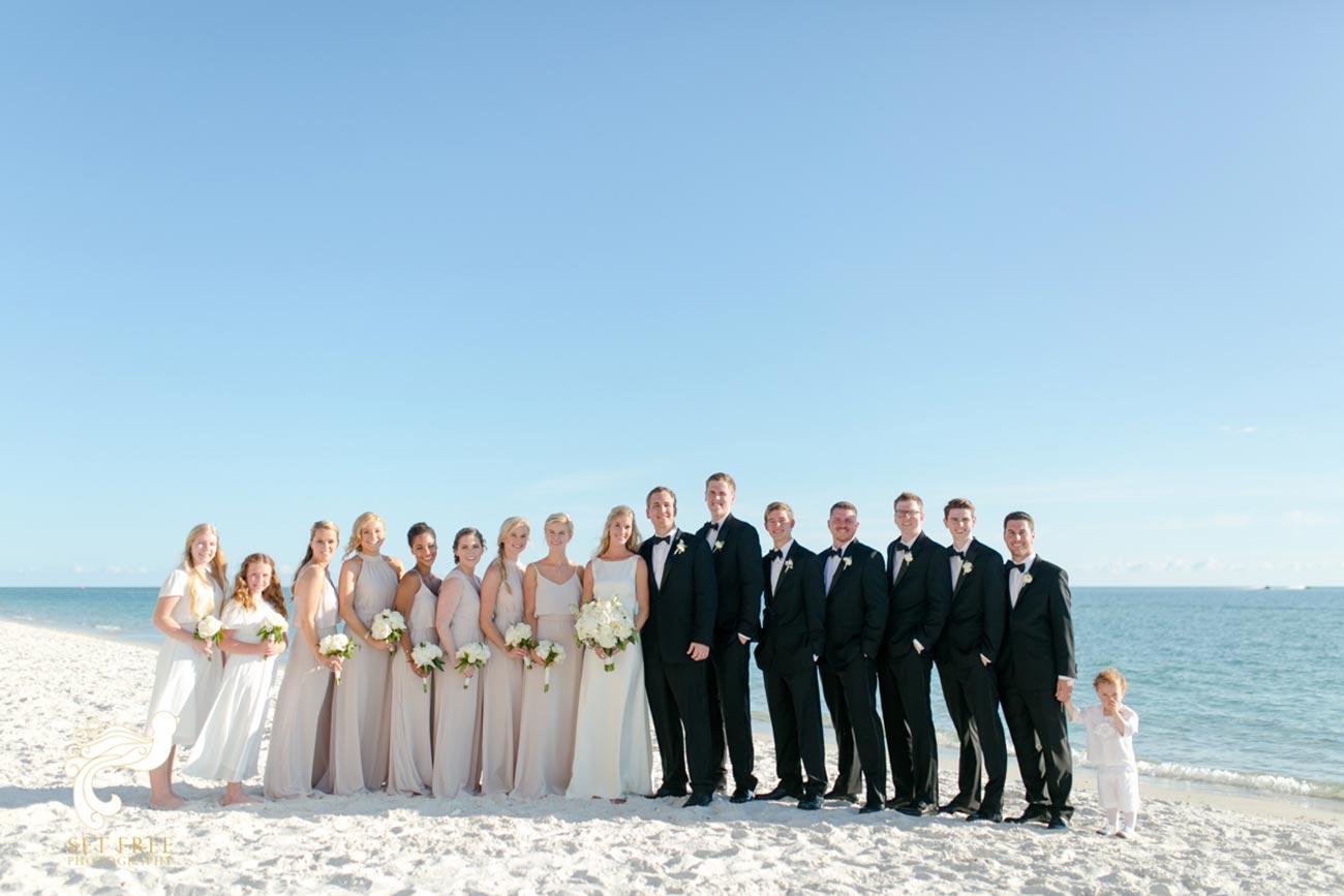 Brides and groom, bridesmaids and groomsmen on the beach