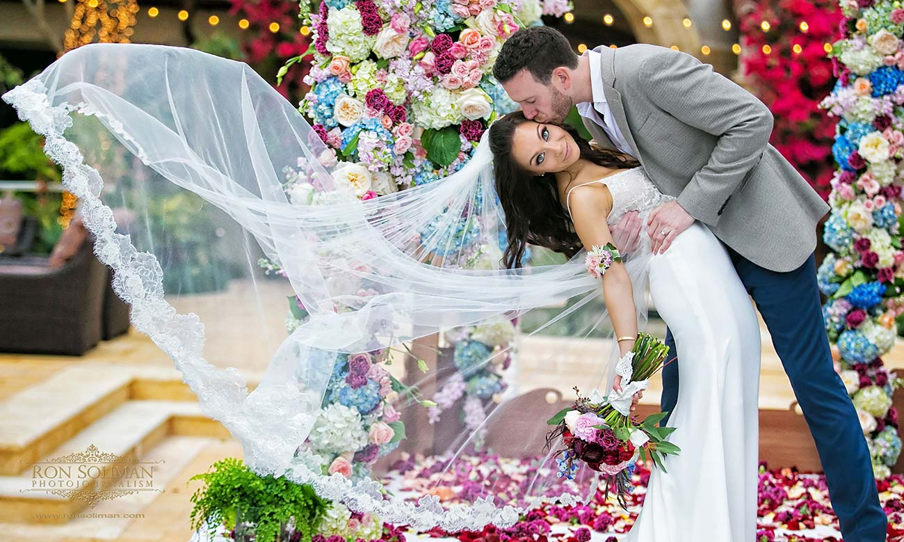 Bride and groom kissing, with bride's veil flowing beside her