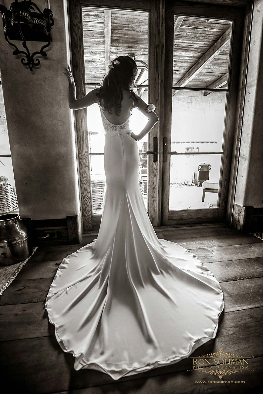 Portrait of the bride from behind as she stands in front of glass doors