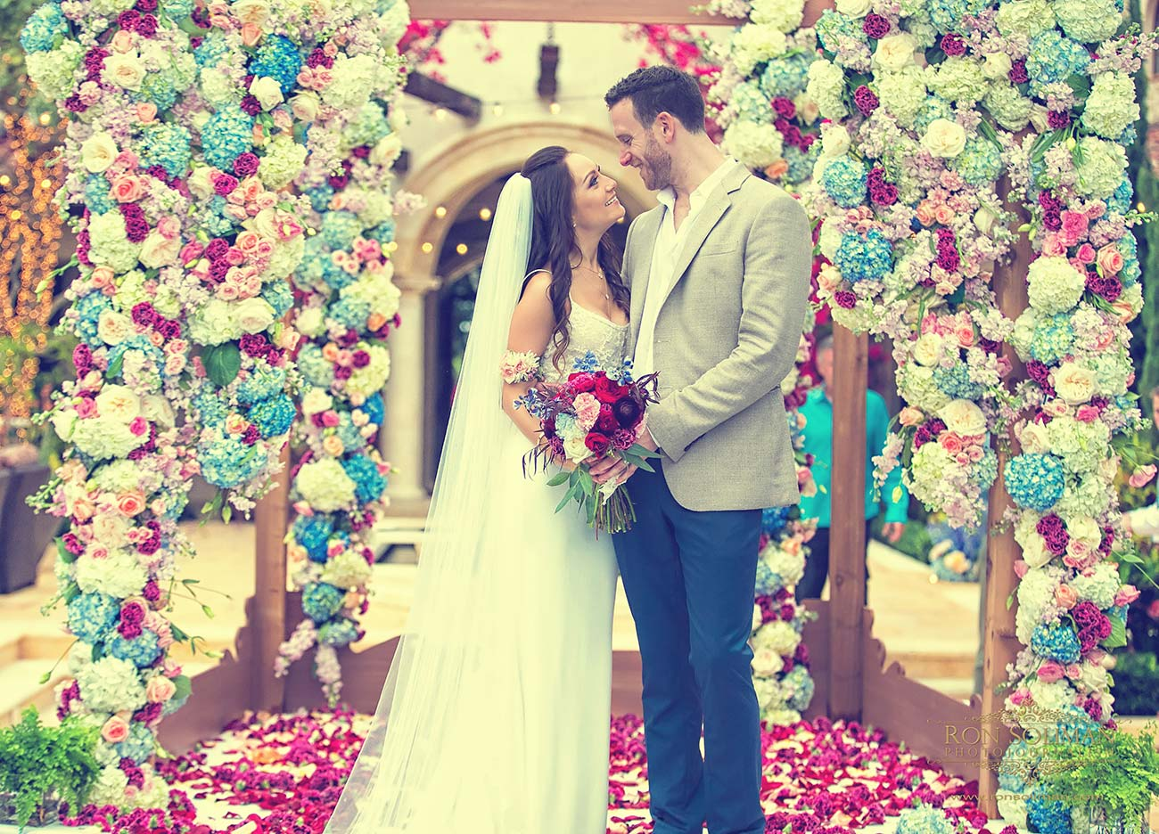 Bride and groom portrait in front of their floral wedding day arbor