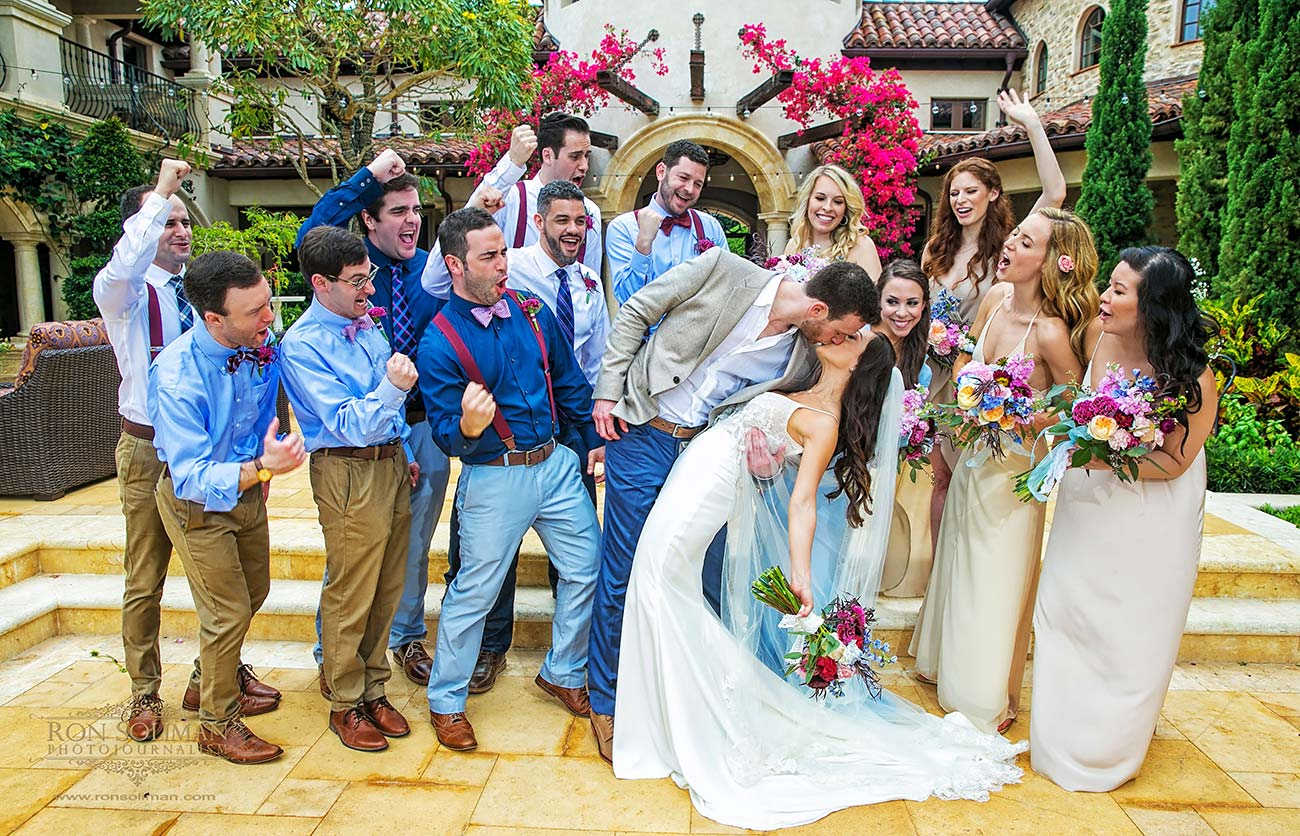 Bride and groom kissing with bridal party behind them cheering on