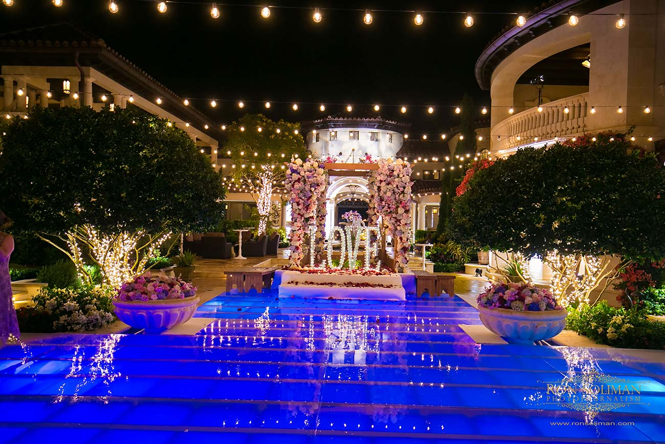 Night time view of pool, uplighting, and the word LOVE lit up with flowers and lights