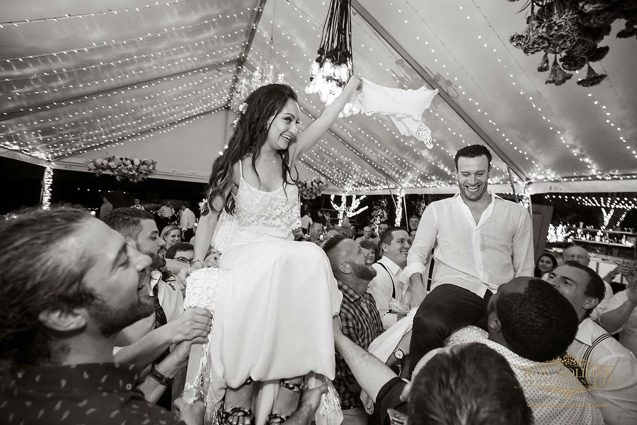 Bride and groom sitting on chairs that are hoisted on guests' shoulders, dancing together