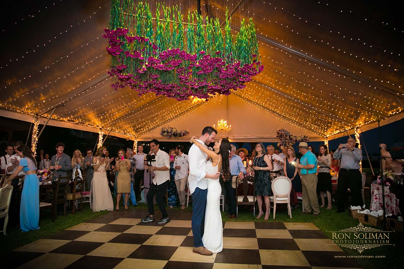 Purple florals, fairy lights and dancing bride and groom surround by clapping guest in their wedding day tent