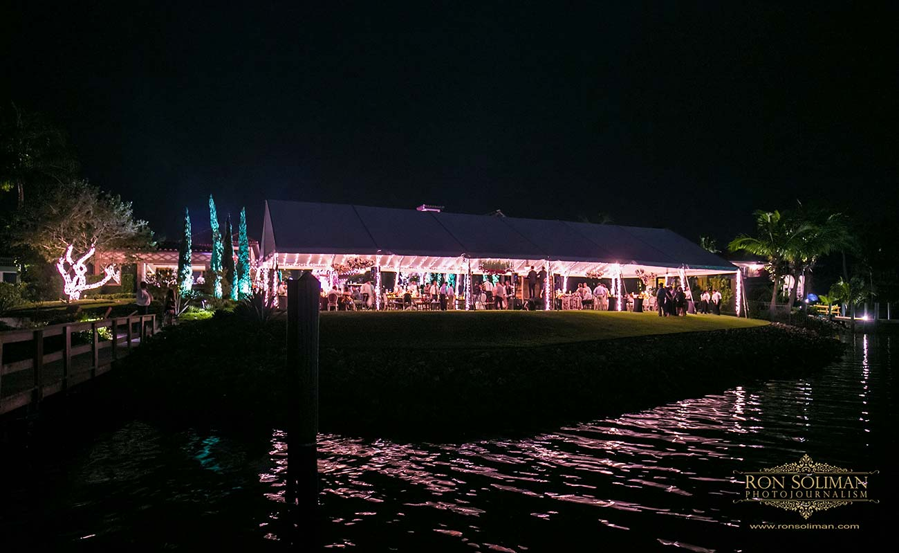 Night time view of a wedding tent with guests and pink uplighting