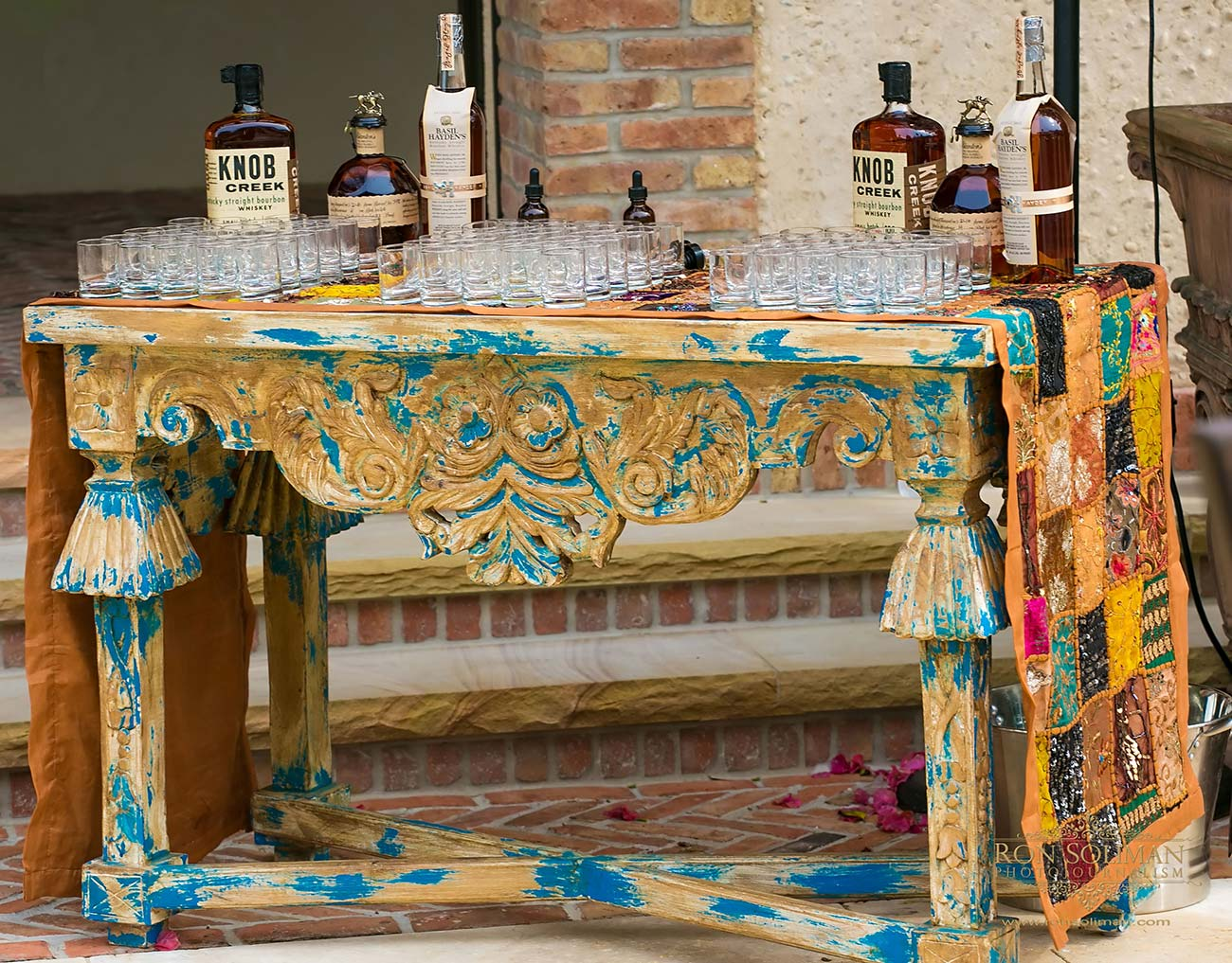 Shabby chic table holding glasses and Knob Creek whiskey bottles