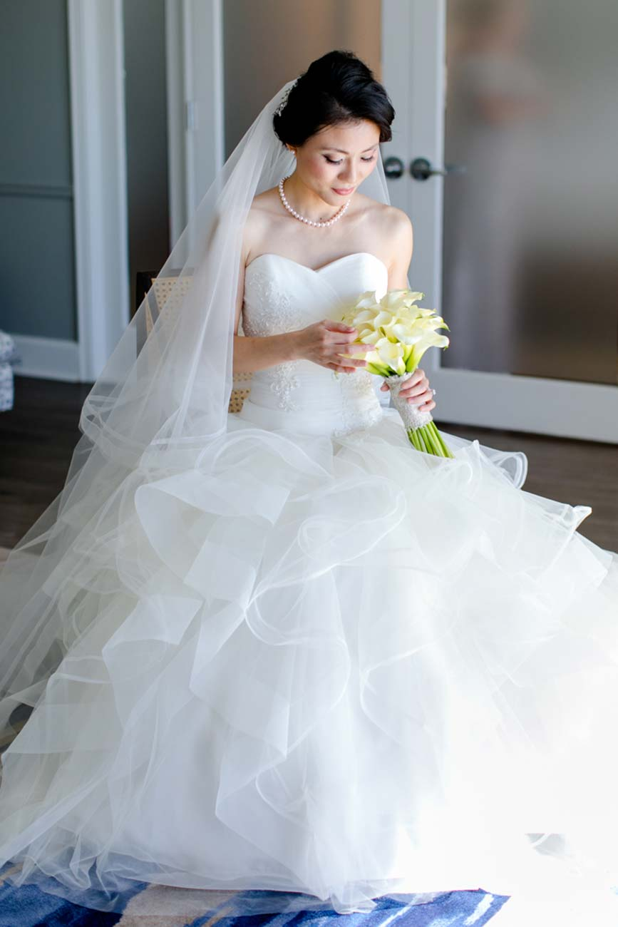 Portrait of a bride, looking at her white bouquet