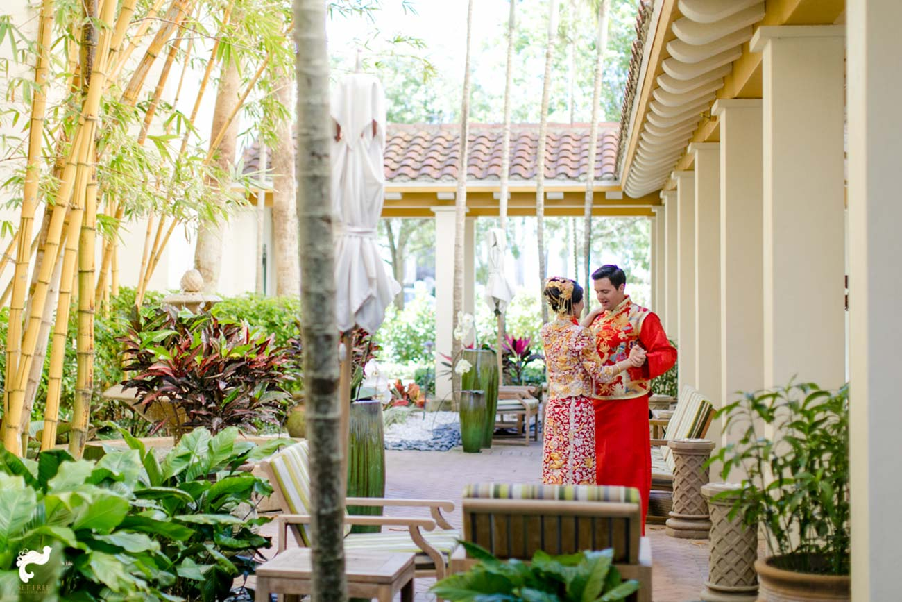 Bride and groom's first look in a landscaped outdoor courtyard