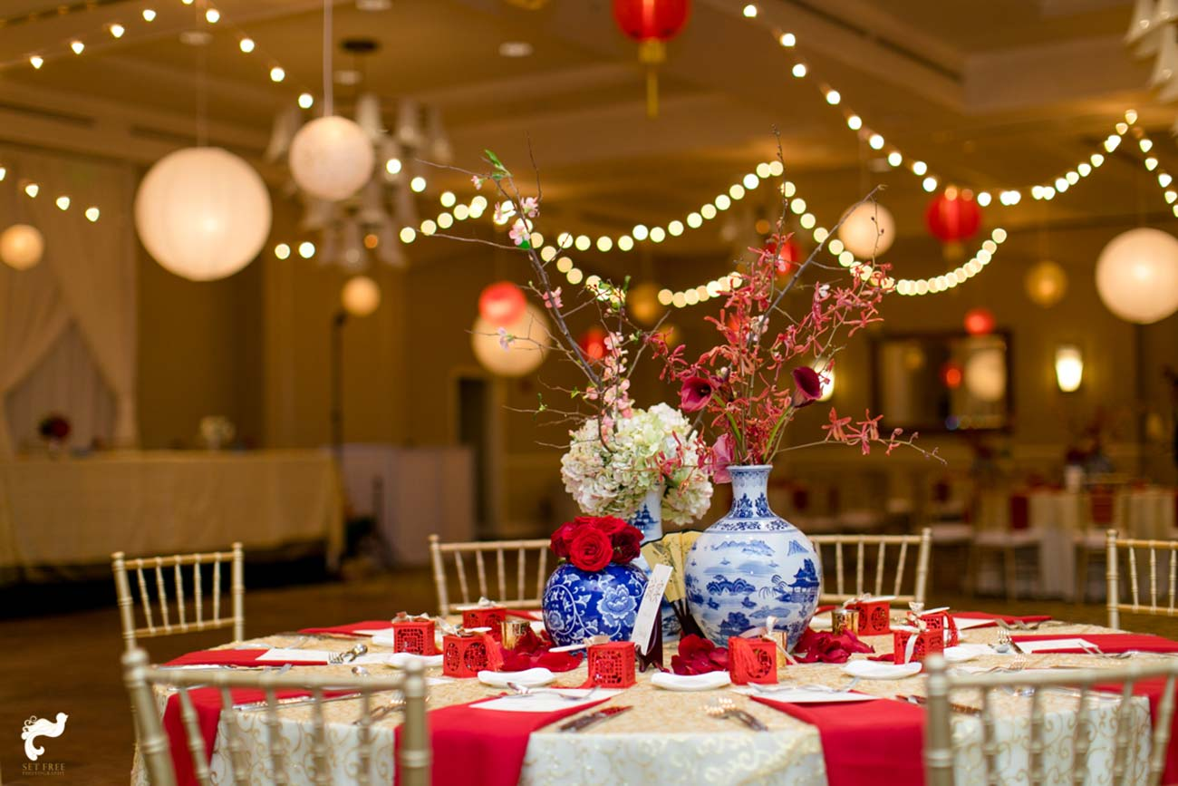 Wedding reception table top design with red, white and blue accents and hanging paper lanterns in the background