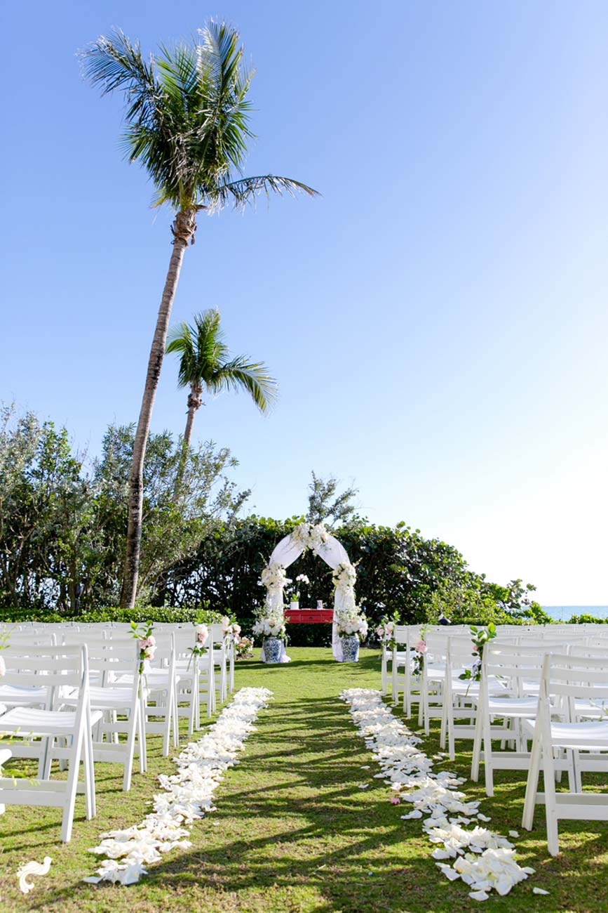 Outdoor wedding ceremony set up by the beach with white petals lining the aisle