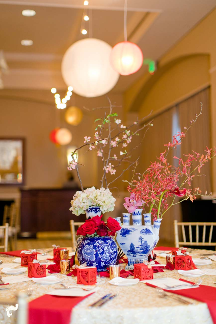 Wedding reception tabletop design with blue and white porcelain, red and white flowers and red accents