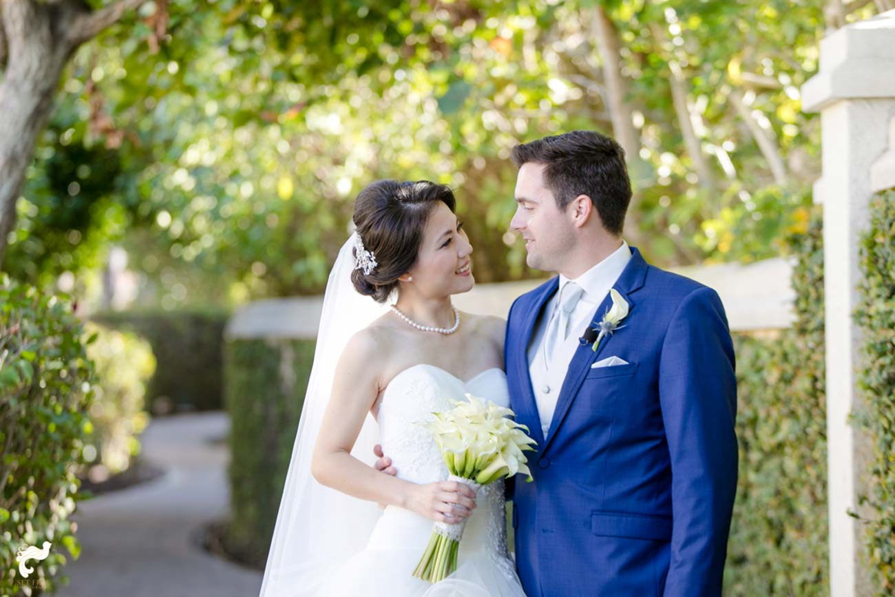 Portrait of bride and groom smiling and looking at each other outside, surrounded by greenery
