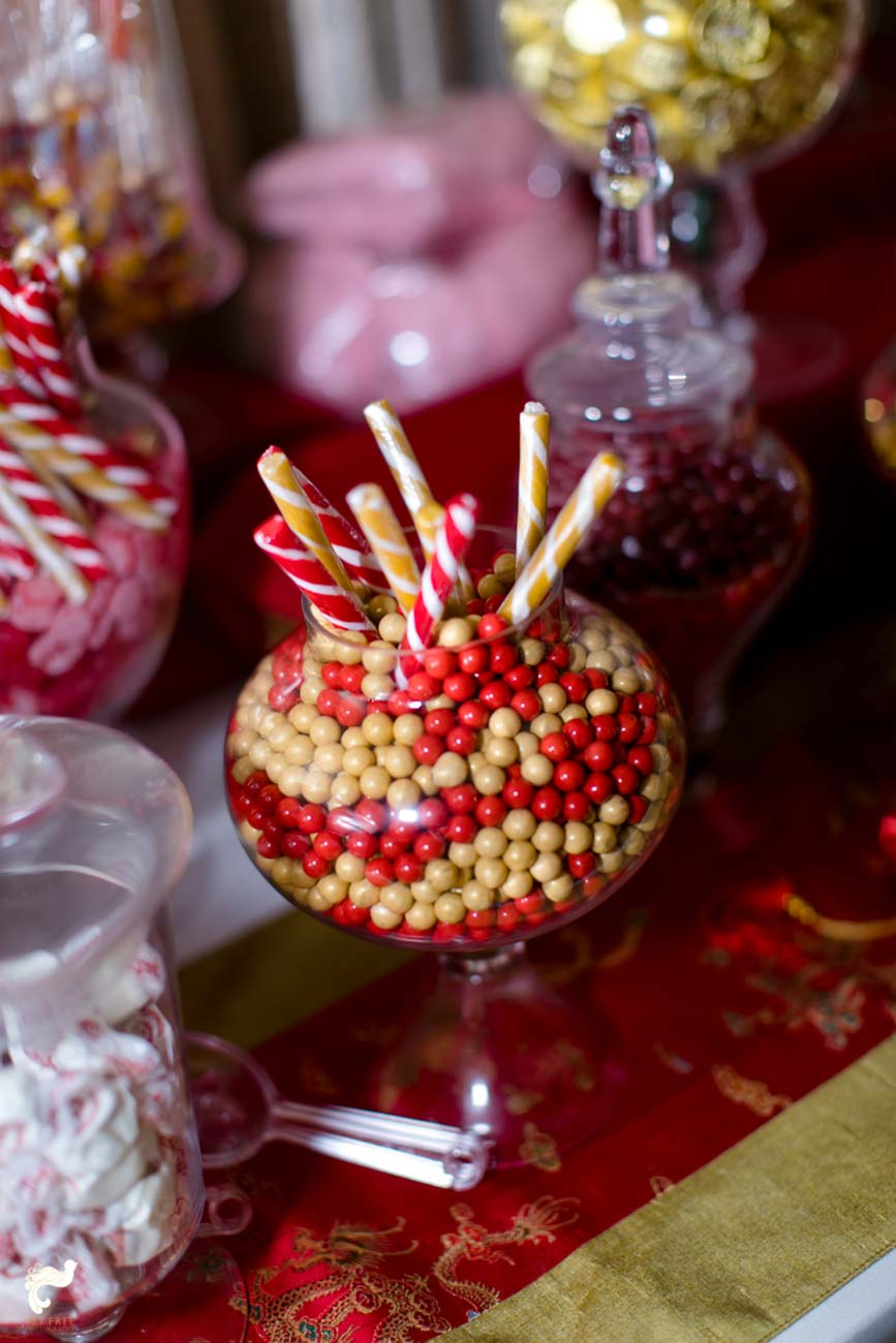 Glass jar filled with red and yellow small candies and candy canes
