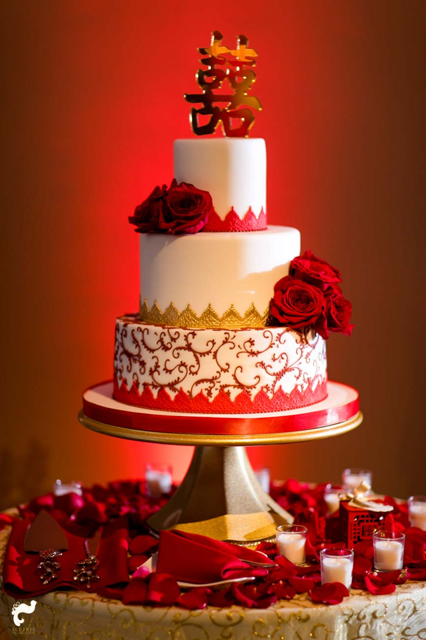 3 tiered white wedding cake with red and gold embellishments surrounded by red petals and tea candles