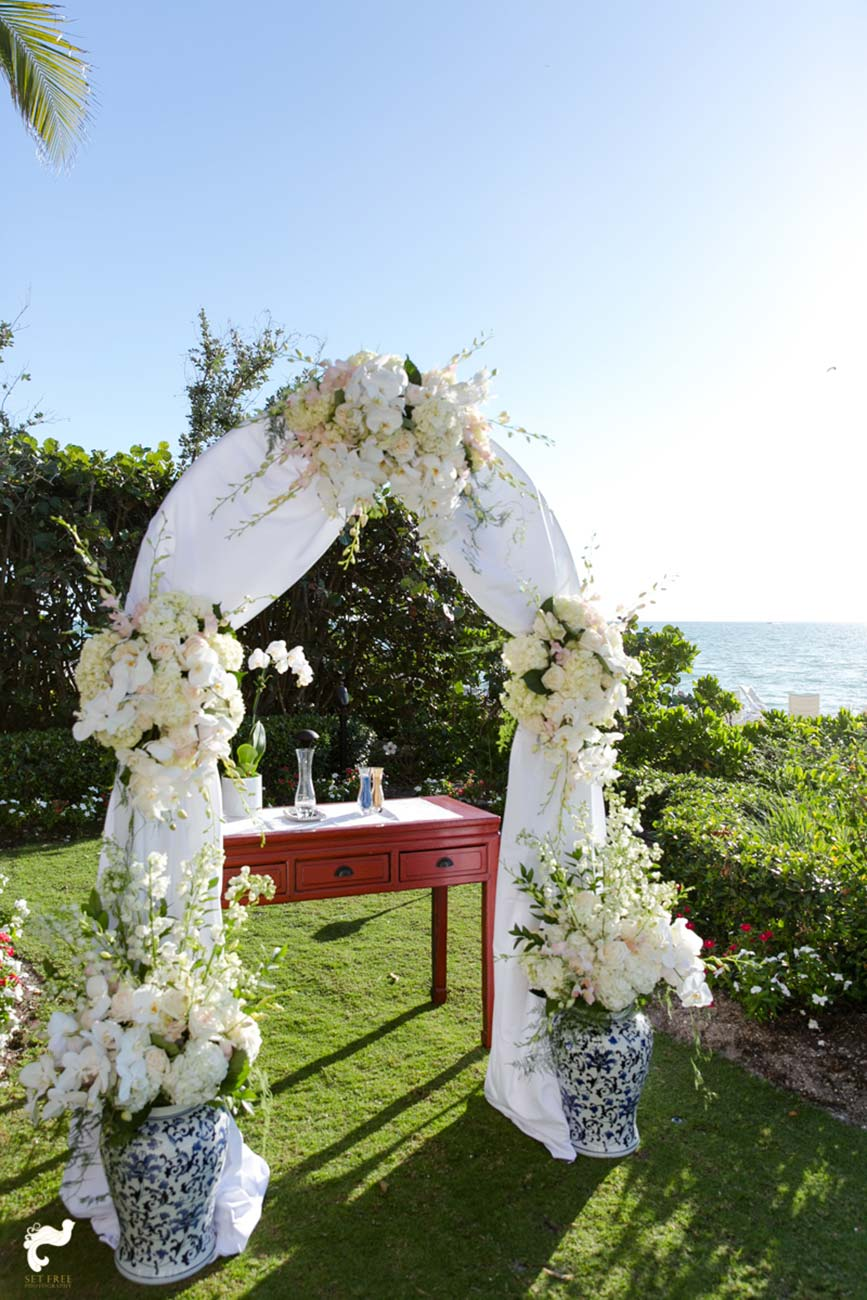 Wedding arbor with white flowers and a red table overlooking the ocean